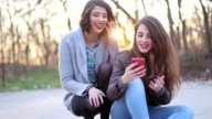 Two hipster girls look in the phone and laughing