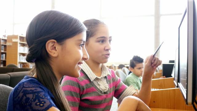 Two Hispanic pre-teen middle school female students are brainstorming ideas in the library of STEM school