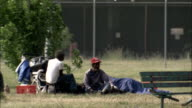Two homeless seniors sit together with their camping gear. Available in HD.