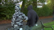 MS PAN Two hooded boys heckling man walking past who turns back to confront them in park / London, England