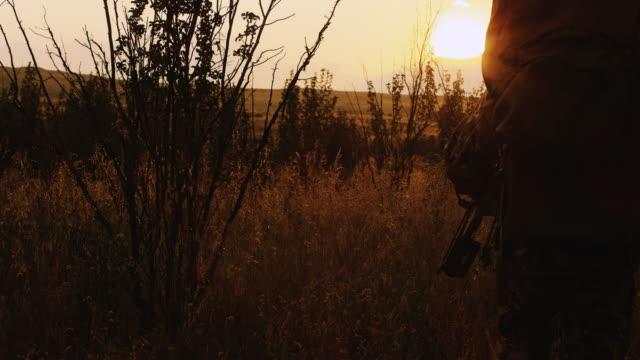Zwei Jäger übergeben von der Kamera, wie sie ihre Beute bei Sonnenuntergang Stengel.