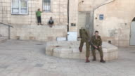 Two IDF soldiers relax next to two young boys NO