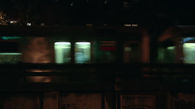 LA Two illuminated elevated trains passing at night, with lights of buildings beyond / New York City, New York, United States