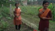 Two Indian women standing in a garden.