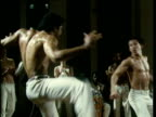 Two jogardors wearing traditional white trousers perform repertoire of high speed front and back spinning kicks handstands cartwheels and leg sweeps during capoeira jogo watched by musicians playing instruments New York 1980's