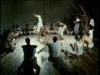 Two jorardors wearing traditional white trousers perform repertoire of front and back spinning kicks handstands cartwheels and leg sweeps during capoeira jogo watched by circle of capoeiristas and musicians New York 1980's