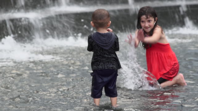 Two kids play in a fountain and splash each other.  The little boy runs off.