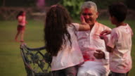 Two kids playing holi festival with his grandfather in a lawn