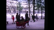 1965 two kids riding in goat-drawn cart in Parisian park
