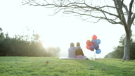 MS Two kids sitting in grass field with balloons / Los Angeles, California, United States