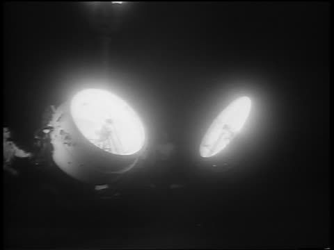 B/W 1951 two large klieg lights pointing at sky rotating at night