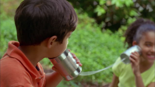 Two Latino children play using tin cans and string as a telephone.