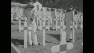 Two lines of sailors of Vichy French Navy facing one another at cemetery large cross and French flag on flagpole in background pan across to rows of...