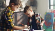 Two little boys painting piggy bank