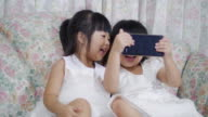 Two Little Girl Using A Mobile Phone