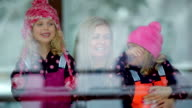 MS PAN Two little girls and one wonan looking out snowy winter day / Whistler, BC, Canada