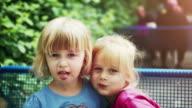 Two Little Girls Eating Hamburger Outside