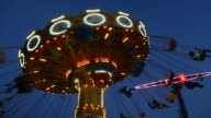 Two lowangle wide shots of a wave swinger turning riders at night at the Steel Pier Amusement Park in Atlantic City New Jersey