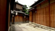 Two maiko wearing summer kimonos walk through an alley.