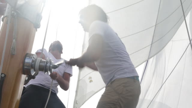 MS Two male crew members winding winch and pulling rope on sailing yacht at sea.
