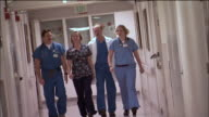 SLO MO, MS, CANTED, Two male doctors and two female nurses walking down hospital hallway