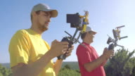 Two male drone operators with remote controllers