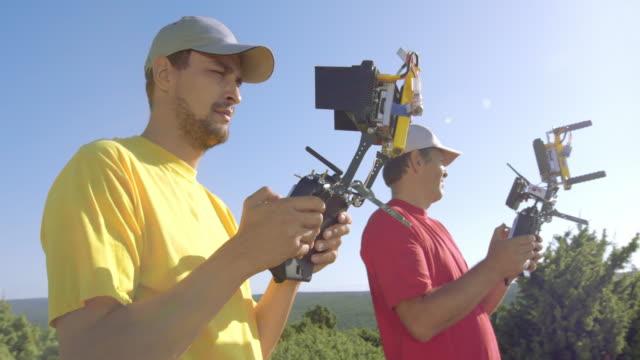 Twee mannelijke drone operators met externe controllers