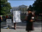1972 two male hippies holding peace posters in front of White House / Washington DC