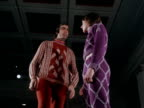 Two male models stand on the catwalk wearing tight brightly coloured and patterned woollen jumpers and trousers 1970