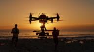 Zwei männliche Operatoren, die Steuerung der Drohne bei Sonnenuntergang