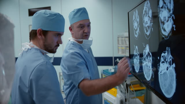 Two male surgeons discussing CT scan of a head