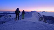 PAN Two man snowshoeing on mountain ridge at dusk