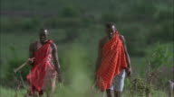 Two Masai hunters talk as they walk. Available in HD.