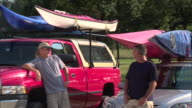 MS Two mature men talking next to pick-up truck with kayaks on roof rack / Texas, USA