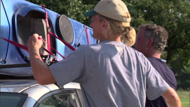 CU PAN ZO MS Two mature men untying kayak from car roof rack / Texas, USA