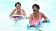 Two mature women doing water aerobics