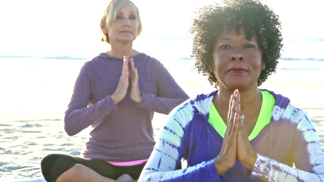 Two mature women in doing yoga on beach, lotus pose