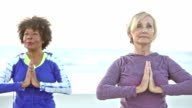 Two mature women in doing yoga on beach