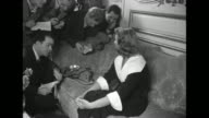 Two medium shots of reporters and photographers crowding around sofa to talk to and take photos of actress HayworthÊ[exact month/day not known]