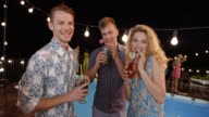 Two men and a woman toasting by the pool at a party and smiling into the camera