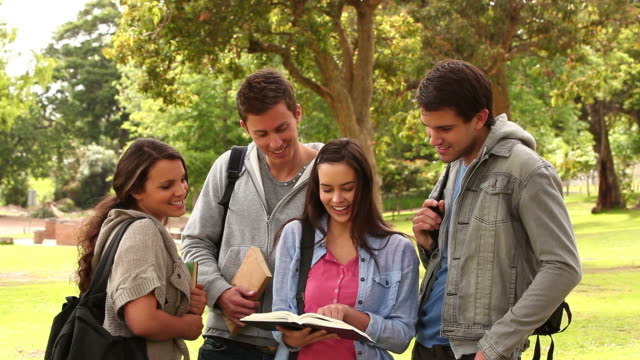 Four friends laughing while pointing at a book as they stand together in a park