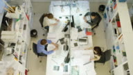 HA WS two men and two women working on  desk in modern office, one man placing phone call