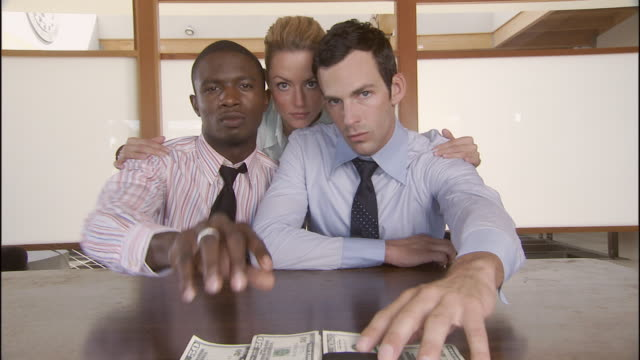 MS, Two men and woman sliding stack of cash across table, portrait, Los Angeles, California, USA