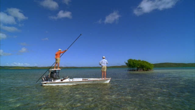 WS, Two men bone fishing from flat boat, rear view, Vieques, Puerto Rico