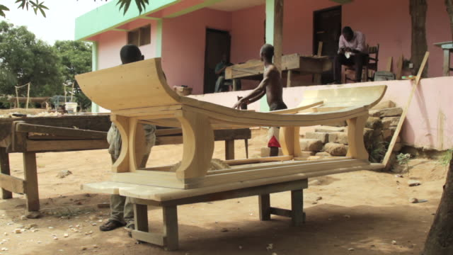 Two men build a coffin in the city of Accra.