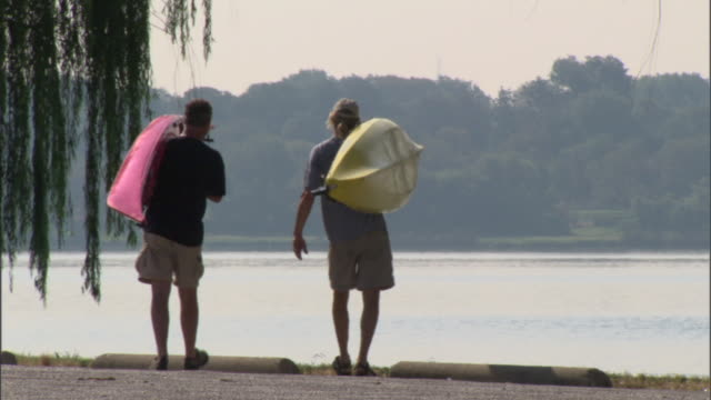 WS Two men carrying kayaks and setting them down at edge of lake / Texas, USA