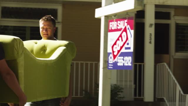 MS PAN Two men carrying sofa into house, woman carrying cardboard box / Provo, Utah, USA