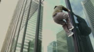 MS LA TD TU Two men climbing shop window in office building, performing parkour, Vancouver, British Columbia, Canada