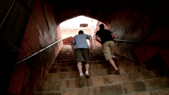 Two men climbing stone stairs to ancient building.
