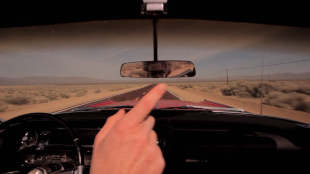 Two men cruise down a desert highway outside of Las Vegas in a red vintage convertible.